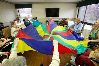 Team of older people playing with an open parachute