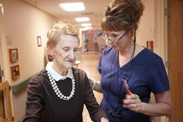 A nurse assisting an older woman down the hallway