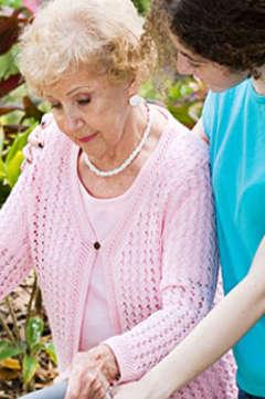nurse helping older woman walk