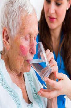 nurse helping an elderly woman drink water
