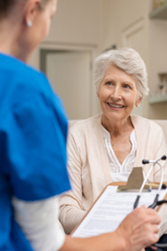 older woman speaking with nurse