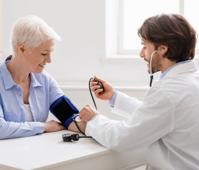 doctor taking an older woman's blood pressure